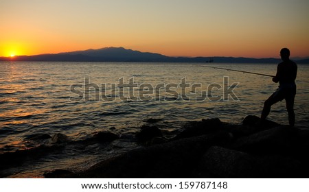 angler fishing at sunset. mountain in background - stock photo