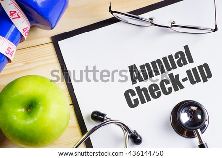 """""""Annual check-up"""" text on paper with blue dumbbell, stethoscope, spectacles, measurement tape and delicious green apple on wooden table - medical, health and disease concept - stock photo"""