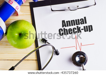 """""""Annual Check-up"""" text on paper with heart beat diagram, stethoscope, delicious green apple, measurement tape and blue dumbbell on wooden table - medical, health and disease concept - stock photo"""