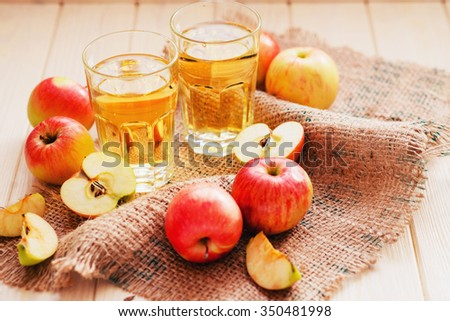 apple cider with fresh apples , cinnamon , spices and chips on a wooden background - stock photo
