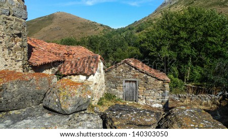 architecture and rustic. Roofs surrounded by mountains and vegetation with rocks in the foreground. Irede. Leon. Spain - stock photo
