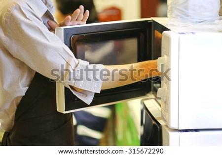 arm pick up food inside microwave oven, waiter warming food with microwave in fast food shop and restaurant, beverage and kitchen tool equipment.
