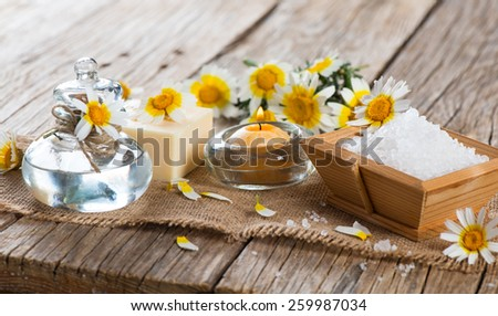 Aroma spa with chamomile flowers on a old wooden background - stock photo