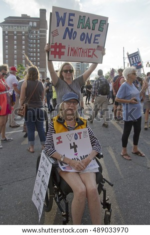 "Asheville, North Carolina: September 12, 2016: Women, one in a wheelchair, hold protest signs at a Trump rally, one saying ""We Hate No One, I'm With Her"" on September 12, 2016 in Asheville, NC"