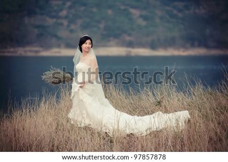 asian bride in her wedding dress - stock photo