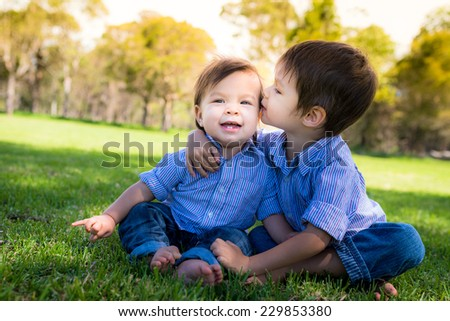 2 Asian Caucasian mixed race toddler brothers hug and kiss outside on a park - stock photo