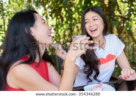 Asian Women friend talking, laughing and holding coffee cups and cake at outdoor cafe - communication and friendship concept