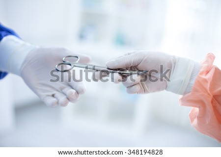 assistant adds surgeon instruments during surgery, close up of hands in glove holding  scissors - stock photo