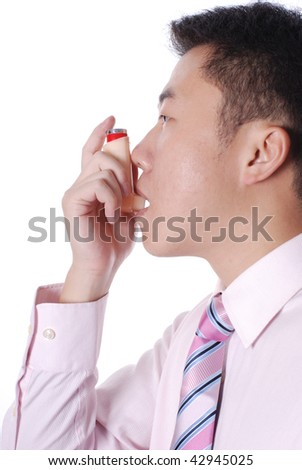 Asthma inhaler being used by Asian man - stock photo