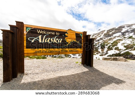 "At Mile 14.7 from Skagway ferry dock on South Klondike Highway, the ""Welcome to Alaska"" sign appears with large parking area on the left. - stock photo"