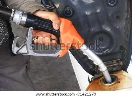 At the gas station pump putting gas into the motorcycle - stock photo