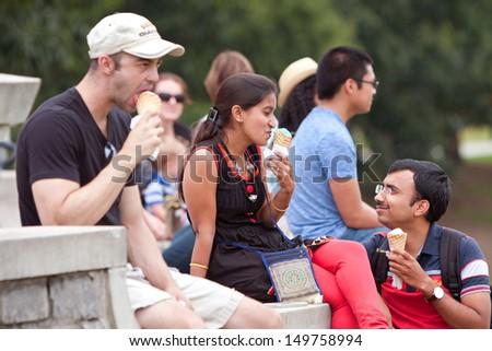 ATLANTA, GA - JULY 27: Young adults enjoy eating ice cream cones at the 3rd Annual Atlanta Ice Cream Festival at Piedmont Park, on July 27, 2013 in Atlanta.    - stock photo