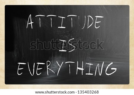 """Attitude is Everything"" handwritten with white chalk on a blackboard"