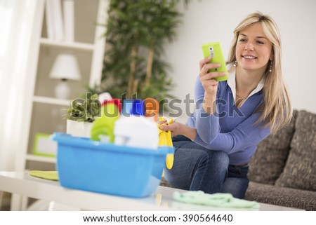 Attractive blond woman look at mobile phone during break from cleaning house - stock photo