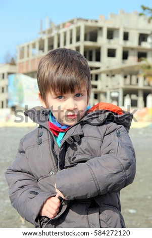 attractive cute little stylish boy with brown shining fashion haircut at the walk  in the sea coast  in sunny good day in winter