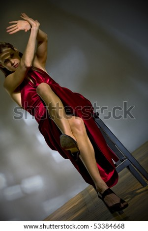 Attractive woman in red dress sit on the chair closing from blinding rays of light - stock photo