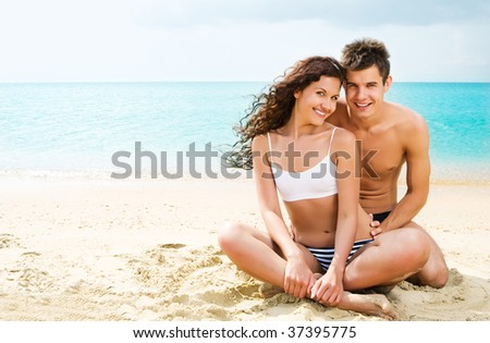 Attractive young couple relaxing on the beach - stock photo