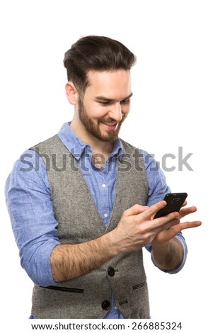 Attractive young guy looking at his smart phone while text messaging isolated on white background - stock photo