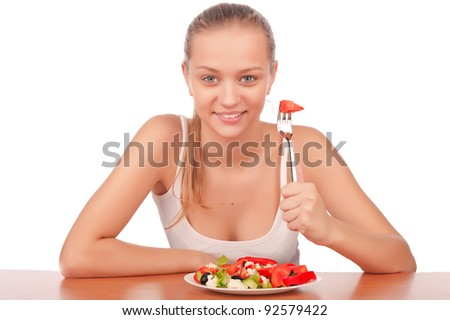attractive young woman eat vegetarian salad at table, isolated on white