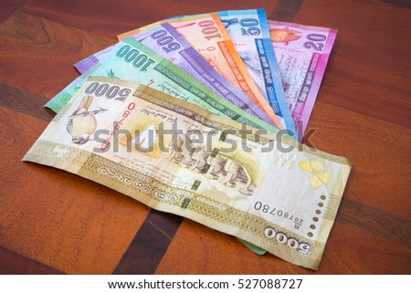 21 August 2015 - Sri Lanka. Kalutara. The national currency of Sri Lanka. Rupee. Banknotes are folded like a fan on the wooden table.
