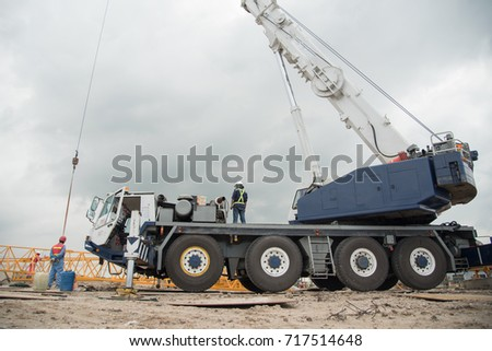 automobile crane with risen telescopic boom outdoors over blue sky