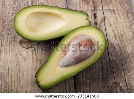 Avocado  cut in half on old brown wood - stock photo