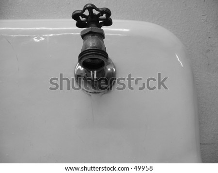 ( B&W ) A Drip of Water from a Laundry Sink Faucet - stock photo