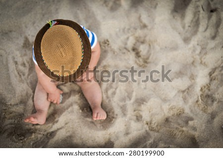 baby boy with a hat sitting on the beach - stock photo