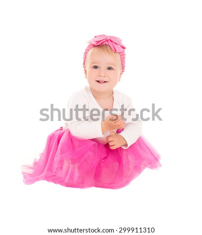 baby girl blonde sits and smiling in a pink tutu skirt, isolated on white background - stock photo