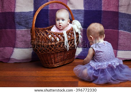 Baby girl is sitting in a wicker basket, the second girl sitting next