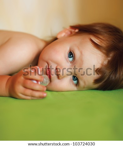 Baby girl with a pacifier in her mouth - stock photo
