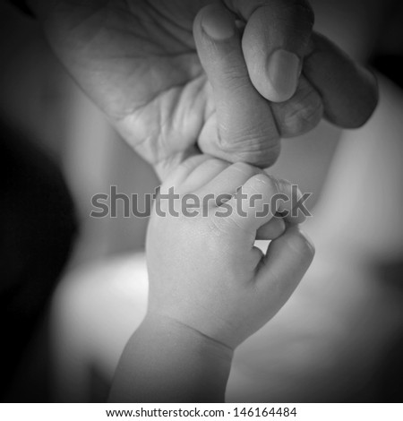 Baby hand gently holding adult's finger - stock photo