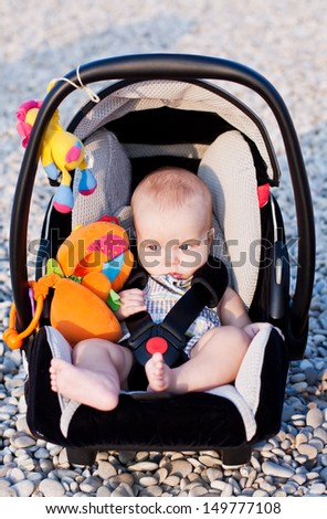 baby in the car seat on the beach on a sunny day - stock photo