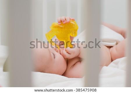 baby in the crib gnawing teeth teether - stock photo