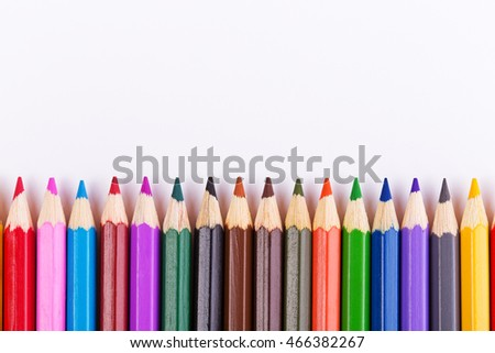 Back to school.Colored pencils in a row on a white background. Top view with copyspace