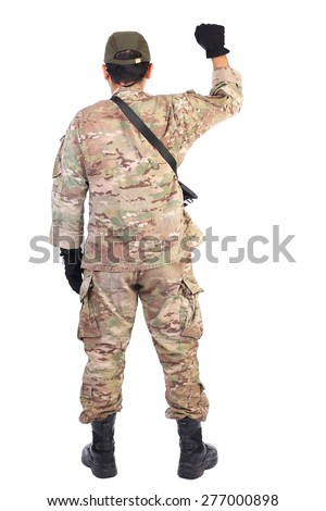 Back view of a soldier with gun holding his arm up over white background - stock photo