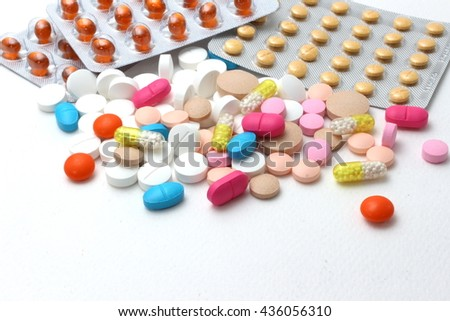 Background of assorted pharmaceutical capsules and medication in different colors denoting different drugs and antibiotics in a health care concept