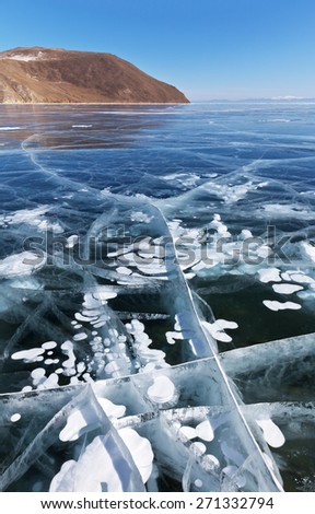 Baikal Lake in winter. White bubbles and cracks in transparent ice - stock photo