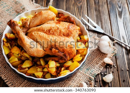 Baked chicken with baked potatoes , apples , garlic and spices on a wooden background - stock photo