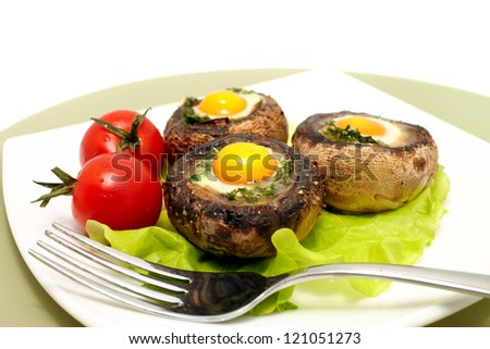 Baked mushrooms with quail`s eggs and tomatoes