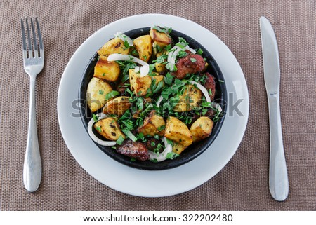 baked roast potatoes with meat in a clay bowl