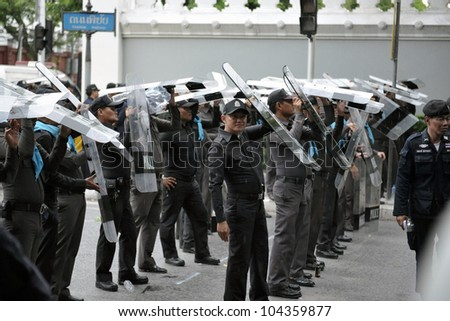 BANGKOK - MAY 31: Policemen stand guard at a barricade during an anti-goverment People's Alliance for Democracy, or yellow-shirt, rally outside Parliament on May 31, 2012 in Bangkok, Thailand.