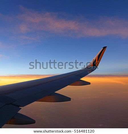 BANGKOK, THAILAND - NOV 3: Tiger airway plane, view of airplane wing floating in mid-air with beautiful sunset on November 3, 2016. Plane approaching the Don Muang Airport in Bangkok come from Taiwan