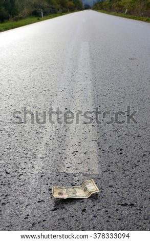 Banknote of a dollar on the middle of the road