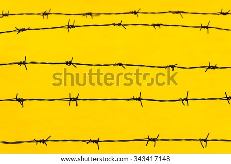 Barbed wire security metal fence on yellow background - stock photo