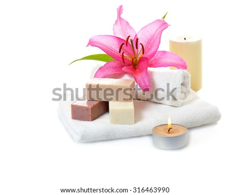 bars of herbal spa soap with white towels,candles and flower