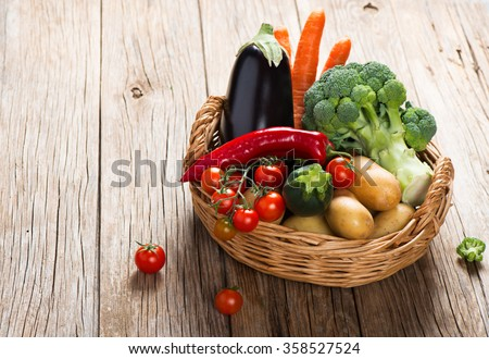Basket full of mixed of useful vegetables on a wooden background - stock photo