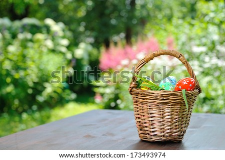 basket with painted eggs standing on garden table