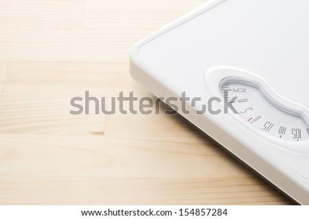 Bathroom scale on a wooden floor - stock photo