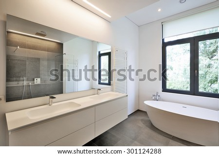 Bathtub in corian, Faucet and shower in tiled bathroom with windows towards garden - stock photo